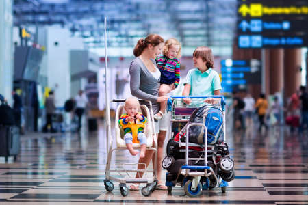Family traveling with kids. Parents with children at international airport with luggage in a cart. Mother holding baby toddler girl and boy flying by airplane. Travel with child for summer vacation.