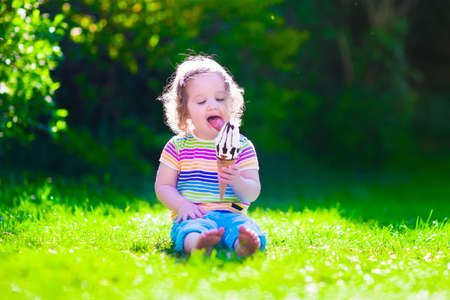 preschooler: Child eating ice cream. Kids play outdoors enjoying sweet snack on a hot summer day. Children eat icecream. Toddler kid playing in the garden. Little girl with vanilla and chocolate ice cone.