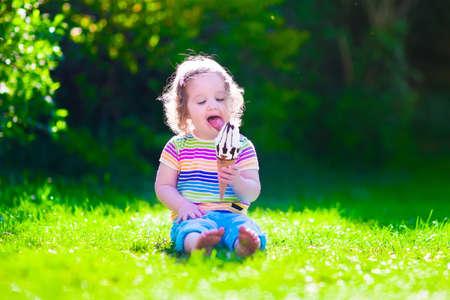 comiendo helado: Niño comiendo helado. Los niños juegan al aire libre disfrutando dulce merienda en un día caluroso de verano. Los niños comen helado. Niño del niño que juega en el jardín. Niña con el cono de vainilla y chocolate hielo. Foto de archivo