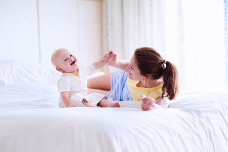 girl bonding: Mother and baby relaxing in white bedroom Stock Photo