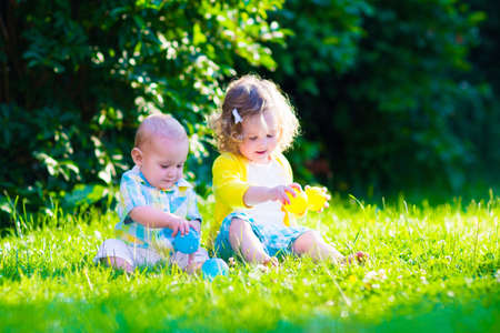 kinder: Niños jugando en el jardín. Chico Niño y pequeño bebé juegan al aire libre en verano. Los niños y niñas con pelotas de juguete en la guardería o jardín de infancia. Niño con la bola de colores. Juguetes al aire libre para los niños. Foto de archivo