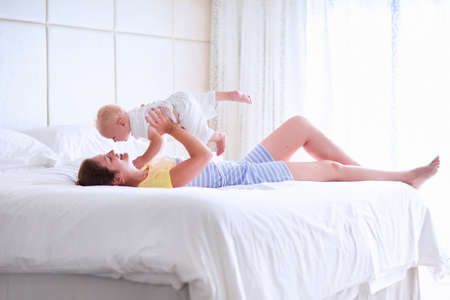 Mother and baby in bed. Young mom playing with her newborn son. Child and parent together at home. Family with kids in the morning. Woman relaxing with kid in a sunny bedroom. Happiness and motherhood
