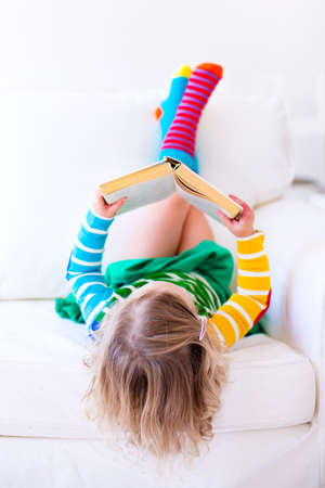 day book: Little girl reading a book relaxing on a white couch. Kids read books at home or preschool. Children learning and doing homework after school. Child playing. Toddler kid in colorful dress on a sofa.