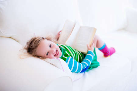 family with one child: Little girl reading a book relaxing on a white couch. Kids read books at home or preschool. Children learning and doing homework after school. Child playing. Toddler kid in colorful dress on a sofa.