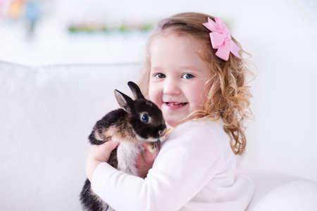 Niño que juega con un conejo real. Los niños juegan con los animales domésticos. Niña sosteniendo conejito. Los niños y los animales en el hogar o preescolar. Cabrito lindo niño rizado abraza a su animal de compañía. Preescolar alimentar conejos.