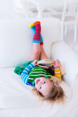 toddler: Little girl reading a book relaxing on a white couch. Kids read books at home or preschool. Children learning and doing homework after school. Child playing. Toddler kid in colorful dress on a sofa.