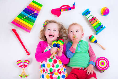 Child with music instruments. Musical education for kids. Colorful wooden art toys for kids. Little girl and boy play music. Kid with xylophone, guitar, flute.