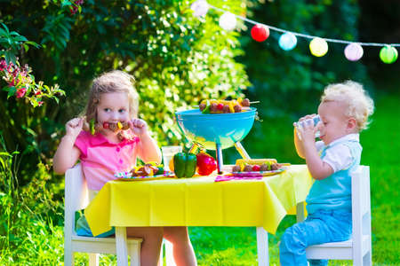 children birthday: Children grilling meat. Family camping and enjoying BBQ. Brother and sister at barbecue preparing steaks and sausages. Kids eating grill and healthy vegetable meal outdoors. Garden party for child. Stock Photo