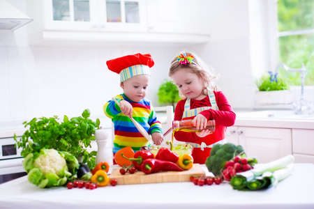 Kids cooking fresh vegetable salad in a white kitchen. Children cook vegetables for vegetarian lunch. Toddler and baby eat healthy dinner. Boy and girl preparing and eating raw meal. Child nutrition.