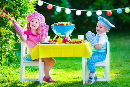 party table: Children grilling meat. Family camping and enjoying BBQ. Brother and sister at barbecue preparing steaks and sausages. Kids eating grill and healthy vegetable meal outdoors. Garden party for child. Stock Photo