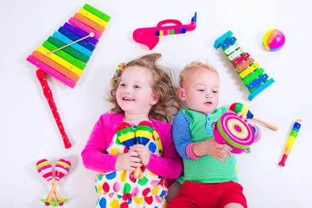Criança com instrumentos musicais. Educação musical para crianças. Brinquedos coloridos de arte de madeira para crianças. A menina e o menino tocam música. Criança com xilofone, violão, flauta.