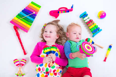niños jugando: Niño con los instrumentos musicales. La educación musical para niños. Juguetes coloridos del arte de madera para niños. La niña y la música del juego del niño. Cabrito con el xilófono, guitarra, flauta.