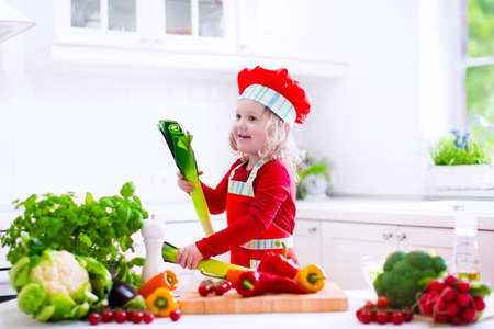 a little dinner: Kids cooking fresh vegetable salad in white kitchen. Children cook vegetables for vegetarian lunch. Toddler in chef hat eats healthy dinner. Little girl preparing and eating raw meal. Child nutrition. Stock Photo