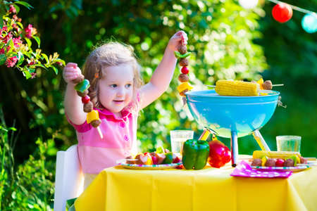 corn meal: Children grilling meat. Family camping and enjoying BBQ. Little girl at barbecue preparing steaks, kebab and corn. Kids eating grill and healthy vegetable meal outdoors. Garden party for toddler child