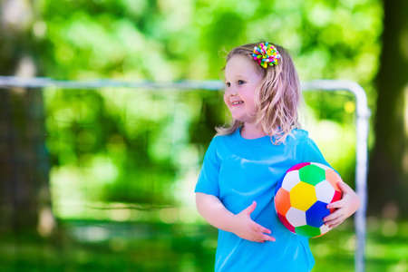 campamento: Dos niños felices jugando fútbol europeo al aire libre en el patio de la escuela. Los niños juegan al fútbol. Deporte activo para el niño preescolar. Juego de bola para el joven equipo chico. Niño y niña marcar un gol en el partido de fútbol. Foto de archivo