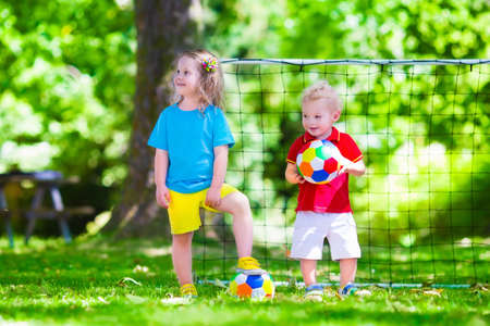 preschool boys: Two happy children playing European football outdoors in school yard. Kids play soccer. Active sport for preschool child. Ball game for young kid team. Boy and girl score a goal in football match.