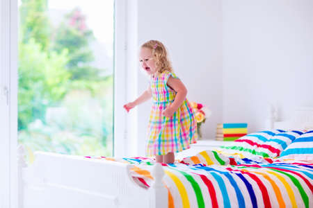 bedding indoors: Little girl jumping on a bed Stock Photo