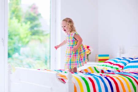 chambre à coucher: Petite fille sautant sur un lit