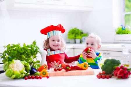 gemelos niÑo y niÑa: Niños que cocinan la ensalada de vegetales frescos en una cocina blanca. Los niños cocinan verduras para el almuerzo vegetariano. Niño y el bebé come la cena saludable. Niño y niña de preparar y comer comida cruda. La nutrición infantil. Foto de archivo