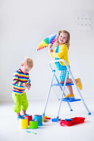 wall painting: Family remodeling house. Home remodel and renovation. Kids painting walls with colorful brush and roller. Children paint wall. Choice of bright color on sample palette for child nursery or kid room. Stock Photo