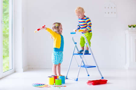 Family remodeling house. Home remodel and renovation. Kids painting walls with colorful brush and roller. Children paint wall. Choice of bright color on sample palette for child nursery or kid room. Archivio Fotografico