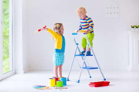 gemelos ni�o y ni�a: Familia remodelaci�n de casa. Inicio remodelaci�n y renovaci�n. Ni�os paredes con colores brocha y rodillo de pintura. Los ni�os pintan la pared. Elecci�n de color brillante en la paleta de muestras para la guarder�a infantil o el sitio del ni�o.