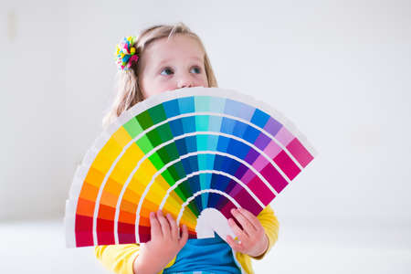 Family remodeling house. Home remodel and renovation. Kids painting walls with colorful brush and roller. Children paint wall. Choice of bright color on sample palette for child nursery or kid room. Stock Photo