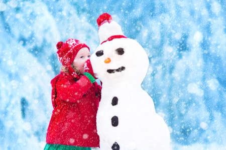 Funny little toddler Dziewczynka w czerwonym kapeluszu i nordic dzianiny ciepły płaszcz grając w śniegu. Dzieci grają na zewnątrz w zimie. Dzieci zabawy w czasie świąt. Dziecko na Boże Narodzenie bałwan budynku.