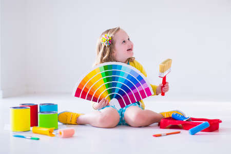 paint palette: Family remodeling house. Home remodel and renovation. Kids painting walls with colorful brush and roller. Children paint wall. Choice of bright color on sample palette for child nursery or kid room. Stock Photo