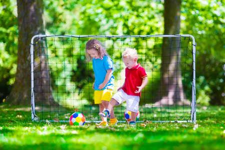 preescolar: Dos ni�os felices jugando f�tbol europeo al aire libre en el patio de la escuela. Los ni�os juegan al f�tbol. Deporte activo para el ni�o preescolar. Juego de bola para el joven equipo chico. Ni�o y ni�a marcar un gol en el partido de f�tbol. Foto de archivo