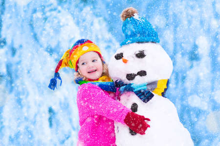 Funny little toddler girl in a colorful hat and warm coat playing with a snow man having fun outdoors in a winter park