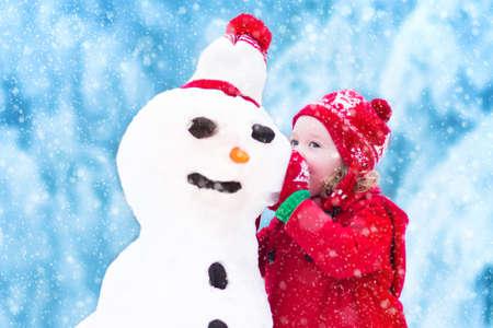 mignonne petite fille: Drôle de petite fille tiddler dans un rouge tricoté chapeau nordique et manteau chaud en jouant avec un amusement bonhomme de neige ayant plein air dans un parc d'hiver