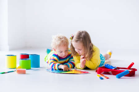 children drawing: Children painting walls at home remodel Stock Photo