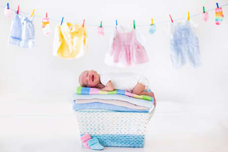 white wash: Newborn baby on a pile of clean dry towels. New born child after bath in a towel. Family washing clothes. Kids wear hanging on a line. Infant apparel, textile for children. Smiling boy after shower. Stock Photo