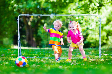 campamento: Dos ni�os felices jugando f�tbol europeo al aire libre en el patio de la escuela. Los ni�os juegan al f�tbol. Deporte activo para el ni�o preescolar. Juego de bola para el joven equipo chico. Ni�o y ni�a marcar un gol en el partido de f�tbol. Foto de archivo