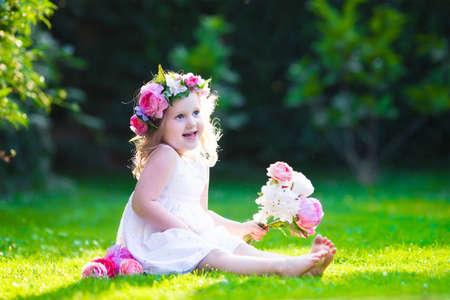 lawn party: Little cute girl with pink flowers. Child wearing a white dress playing in summer garden. Kids gardening. Children play outdoors. Toddler kid with flower bouquet for birthday or mothers day. Stock Photo