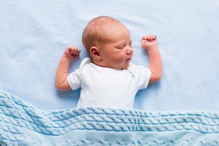 아기: 침대에서 신생아 아기. 파란색 니트 담요 아래에 자고 새로 태어난 아이. 아이들은 잠을. 아이들을위한 침구. 침대에서 유아 낮잠. 곧 출산 후 건강한