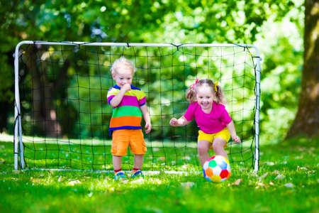 children sport: Two happy children playing European football outdoors in school yard. Kids play soccer. Active sport for preschool child. Ball game for young kid team. Boy and girl score a goal in football match.