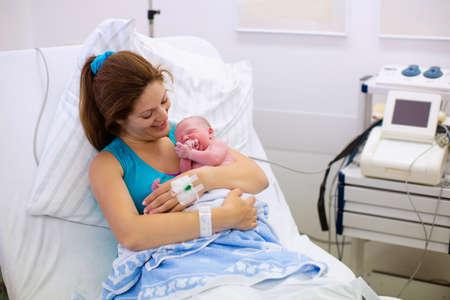 母は赤ちゃんを出産します。分娩室で生まれたばかりの赤ちゃん。ママが労働した後彼女の生まれたばかりの子を保持しています。現代の病院で女