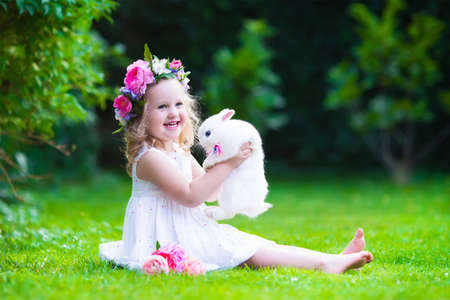 Little girl with real rabbit. Child playing with pet bunny. Kids play with animals. Children at Easter egg hunt. Toddler kid in flower crown and white birthday dress in sunny summer garden.