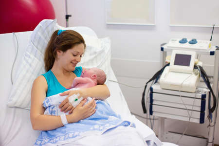 sala parto: Madre che d� alla luce un bambino. Neonato in sala parto. La mamma tiene il suo bambino appena nato dopo il parto. Femmina paziente incinta in un moderno ospedale. Genitori e infantile primi momenti di legame.
