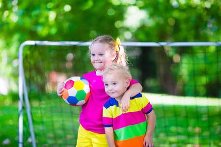 balones deportivos: Dos ni�os felices jugando f�tbol europeo al aire libre en el patio de la escuela. Los ni�os juegan al f�tbol. Deporte activo para el ni�o preescolar. Juego de bola para el joven equipo chico. Ni�o y ni�a marcar un gol en el partido de f�tbol. Foto de archivo