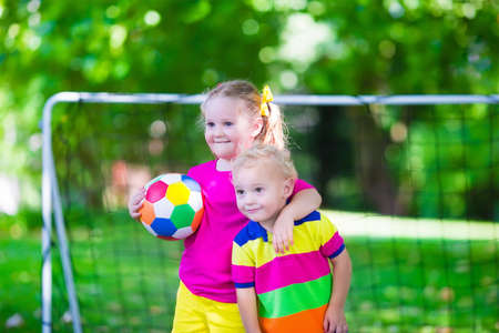 for kids: Two happy children playing European football outdoors in school yard. Kids play soccer. Active sport for preschool child. Ball game for young kid team. Boy and girl score a goal in football match.