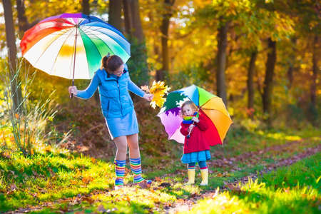 Mother and daughter play in autumn park with golden leaves. Child holding umbrella in the rain. Parent and kid walk in the forest on a rainy fall day. Children playing outdoors with yellow maple leaf