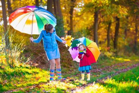Moeder en dochter spelen in de herfst park met gouden bladeren. Kind bedrijf paraplu in de regen. Ouder en kind wandelen in het bos op een regenachtige herfstdag. Kinderen spelen buiten met gele maple leaf