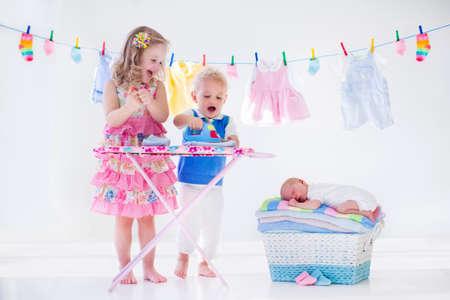 lavanderia: Niño recién nacido en la pila de toallas limpias y secas. Hermano y hermana que juegan con el pequeño hermano. Hermanos unión. Niños planchar la ropa. Gemelas niños jugar con el bebé. Nueva niño nacido después del baño con una toalla