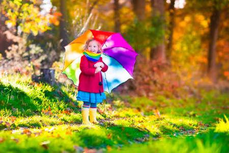 lluvia: Niña que juega en la lluvia en el otoño de parque. Niño que sostiene paraguas caminando en el bosque en un día soleado de otoño. Los niños que juegan al aire libre con la hoja de arce amarillo. Muchacha del niño recogiendo las hojas de oro. Foto de archivo