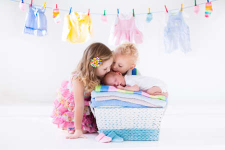 Newborn child on a pile of clean dry towels. Brother and sister kissing little sibling. Siblings bonding. Twin toddler kids kiss baby boy. New born kid after bath in a towel. Family washing clothes. Stock Photo
