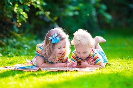niños jugando en la escuela: Niños que leen un libro en el jardín de verano. Estudio de niños. Juego del muchacho y de la muchacha en el patio de la escuela. Amigos en edad preescolar juegan y aprenden. Hermanos hacer la tarea. Niño de Kindergarten y niños pequeños leen libros.