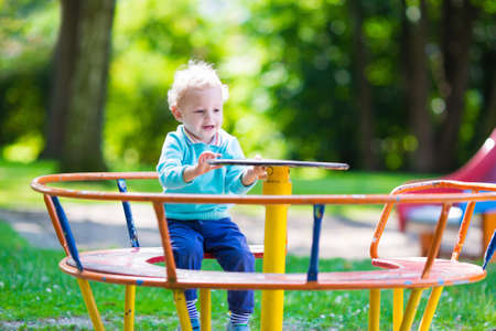 play ground: Little boy on a playground. Child playing outdoors in summer. Kids play on school yard. Happy kid in kindergarten or preschool. Children having fun at daycare play ground. Toddler on a swing.